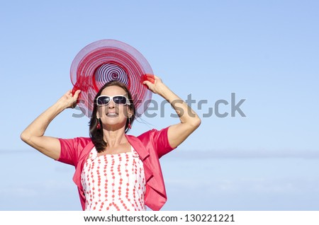 Portrait attractive mature woman happy smiling and closed eyes, joyful outdoor sunny day, isolated with blue sky as background. - stock photo