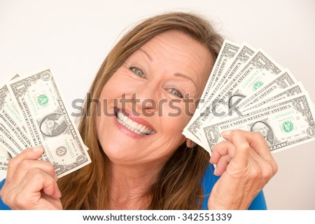Portrait attractive mature woman holding happy relaxed with closed eyes us dollar notes, isolated, bright background.