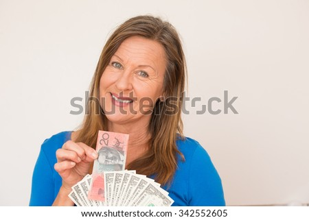 Portrait attractive mature woman holding relaxed Australian and  US dollar notes, isolated, bright background. - stock photo