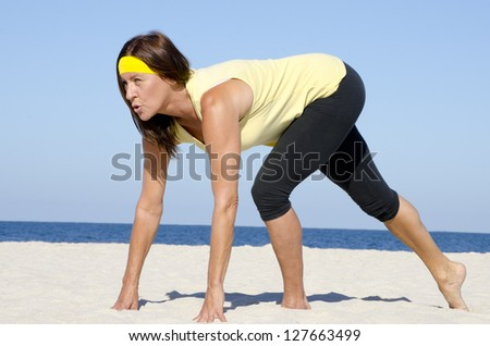 Portrait attractive mature woman living active retirement, stretching exercises at beach, with ocean and blue sky as background. - stock photo