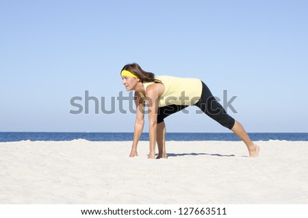 Portrait attractive mature woman living active retirement, stretching exercises at beach, with ocean and blue sky as background and copy space. - stock photo