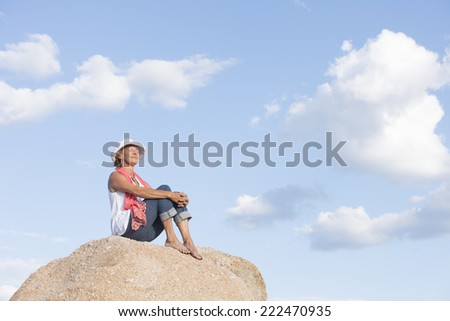 Portrait attractive mature woman sitting thoughtful relaxed smiling on top of rock or mountain with closed eyes, posing in hat and jeans, blue sky as background and copy space. - stock photo