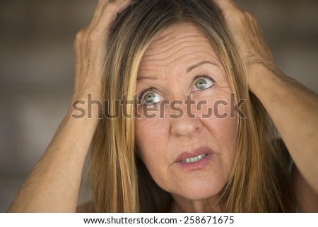 Portrait attractive mature woman, stressed, anxious, scared, unhappy expression, hands covering head, upward look, blurred background. - stock photo