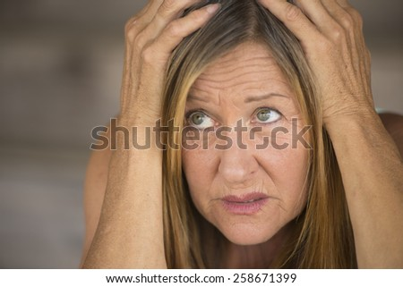 Portrait attractive mature woman, stressed, anxious, scared, unhappy frightened, hands covering head, blurred background. - stock photo