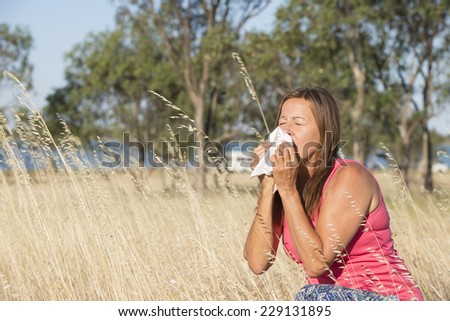 Portrait attractive mature woman suffering from seasonal hayfever allergy, sitting in field of blossoming wheat grass sneezing into handkerchief tissue, blurred outdoor background and copy space. - stock photo