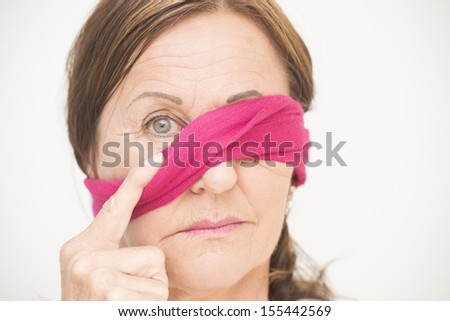 Portrait attractive mature woman with blindfold covering one eye and sad concerned look, isolated on white background. - stock photo
