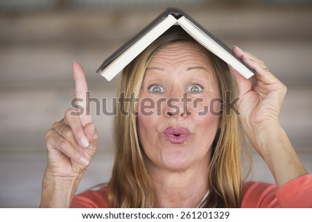 Portrait attractive mature woman with book on head, happy smiling look, finger up pointing, with inspiration and idea, blurred background, copy space. - stock photo