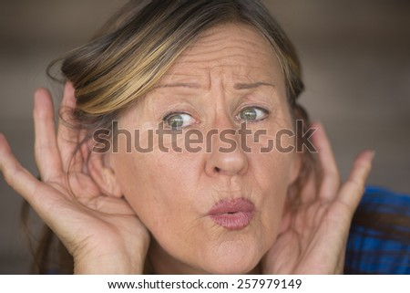 Portrait attractive mature woman with hands at ears listening with curious, interested and surprised facial expression to loud noise or sound, blurred background. - stock photo