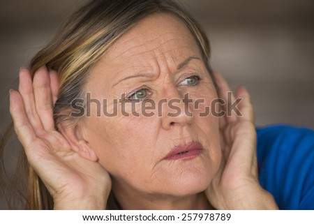 Portrait attractive mature woman with hands at ears listening with curious, interested and worried facial expression to loud noise or sound, blurred background. - stock photo