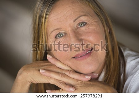 Portrait attractive mature woman with happy relaxed confident expression, thoughtful, serene, blurred background. - stock photo