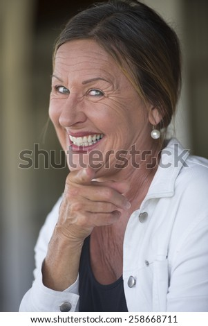 Portrait attractive mature woman with joyful happy friendly expression, confident smiling, finger pointing, blurred background. - stock photo