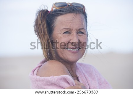 Portrait attractive mature woman with pink towel over shoulder, relaxed happy smiling, bright blurred background outdoor, copy space. - stock photo