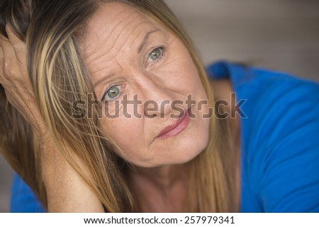 Portrait attractive mature woman with sad, lonely, depressed and stressed facial expression, worried, blurred background. - stock photo