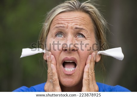 Portrait attractive mature woman with shocked and surprised facial expression, with tissues in ears for noise protection, outdoor blurred background. - stock photo
