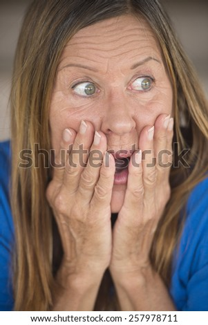 Portrait attractive mature woman with shocked, surprised, anxious, frightened expression, covering mouth with hand, blurred background. - stock photo