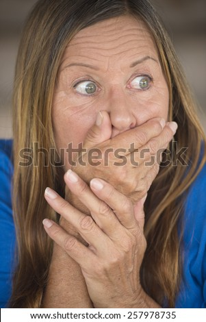 Portrait attractive mature woman with shocked, surprised, anxious, frightened facial expression, covering mouth with hand, blurred background. - stock photo