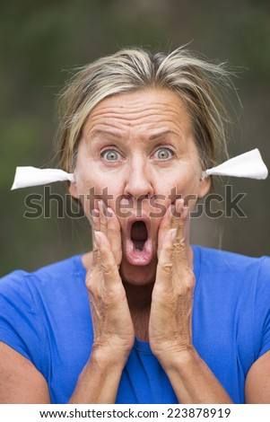Portrait attractive mature woman with stressed shocked facial expression, with tissues in ears for noise protection, outdoor blurred background. - stock photo