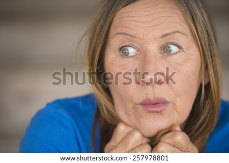 Portrait attractive mature woman with surprised, anxious, fearful facial expression, covering mouth with hand, blurred background. - stock photo