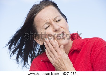 Portrait attractive middle aged woman outdoor in stress and pain, dental problems, suffering from toothache, pressing hands on chin. - stock photo