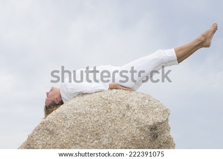 Portrait attractive retired mature woman doing stretching yoga or pilates exercises outdoor on rock, with legs up, body stretched, concentrated, closed eyes, copy space. - stock photo