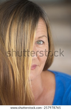 Portrait attractive woman with brunette hair covering half face, one eye confident mysterious upward look, blurred background. - stock photo