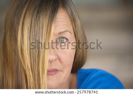 Portrait attractive woman with long brunette hair covering half face, one eye confident serious upward look, blurred background. - stock photo
