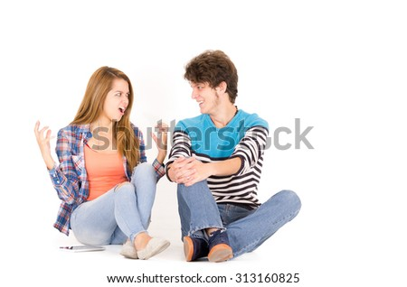 Portrait attractive young happy couple in love, man and woman, isolated over white background sitting on floor looking to each other, she is intense