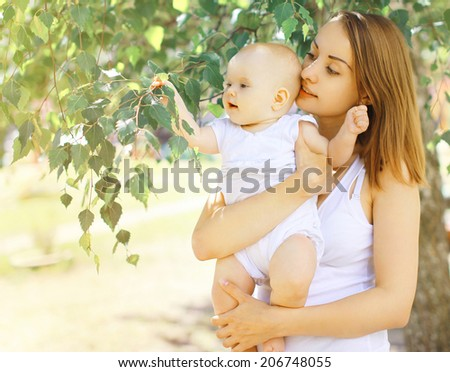 Portrait baby and mother walking in summer day - stock photo