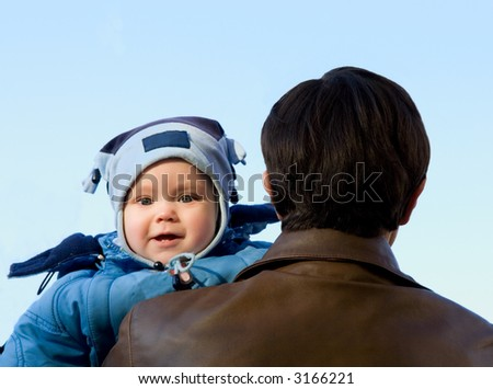 Portrait baby with father. Blue sky. Spring - stock photo