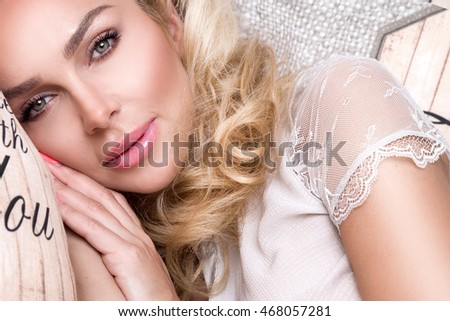 Portrait beautiful blonde woman with a beautiful face and amazing eyes, lies, sleeps on the bed linen in an elegant and sensual looks and flirtatious smile