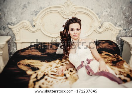 Portrait beautiful bride on bed in wedding day. morning bride. Beautiful bride in white wedding dress lying on the bed in her bedroom.