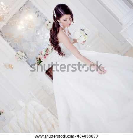 Portrait beautiful bride with a bouquet of flowers. Wedding decoration. Adorable girl holding her skirt