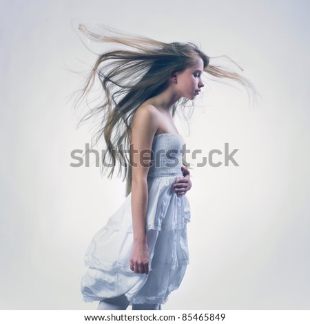 Portrait beautiful girl with flying blond hair in summer white dress - stock photo