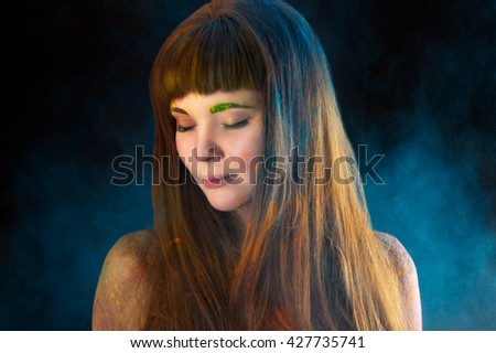 portrait beautiful long-haired girl in colors Holi