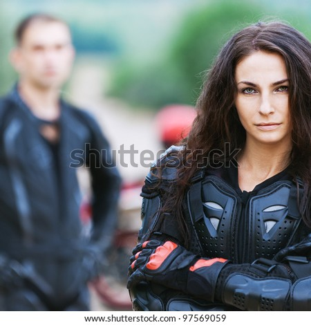 portrait beautiful long-haired woman serious leather jacket gloves background biker guy