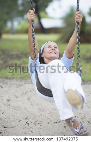 Portrait beautiful looking cheerful mature woman sitting on swing on playground outdoor in park, happy smiling, relaxed laughing, joyful active retirement, with blurred background. - stock photo