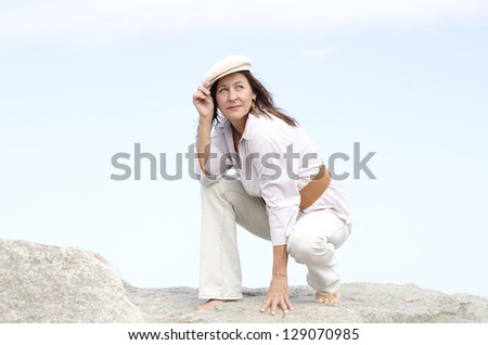 Portrait beautiful looking confident mature woman sitting on rock at ocean outdoor, enjoying active retirement, isolated with cloudy white sky as background and copy space. - stock photo