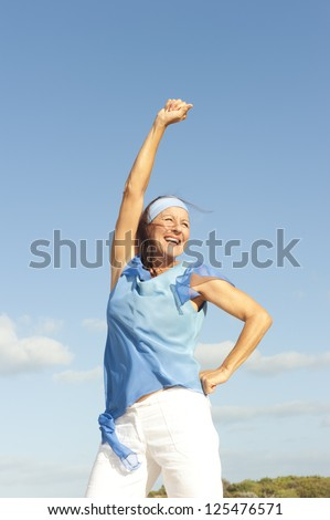 Portrait beautiful looking middle aged woman confident, happy and successful smiling, enjoying active retirement, isolated with blue sky as background and copy space. - stock photo