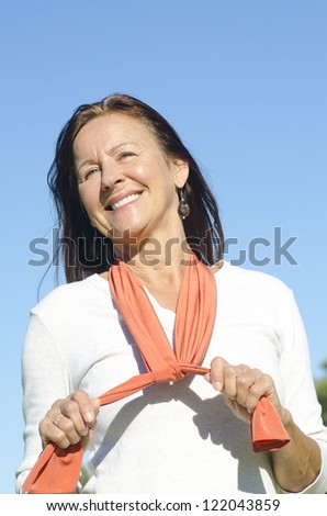 Portrait beautiful looking middle aged woman posing happy smiling sunny outdoor, isolated with blue sky as background and copy space.