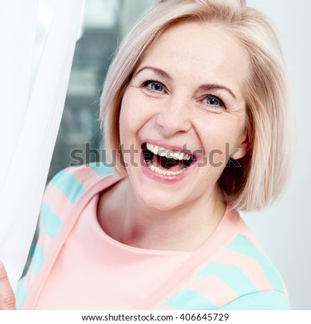 Portrait beautiful middle aged woman smiling friendly and looking into the camera. Woman's face close up - stock photo