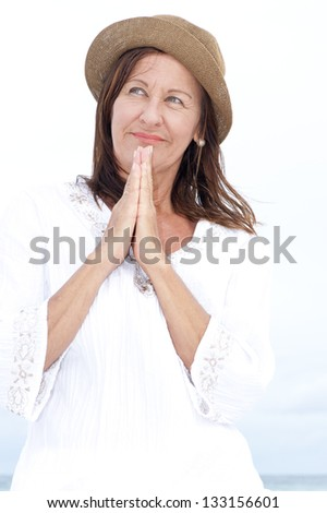 Portrait beautiful middle aged woman with praying hands and thoughtful facial expression standing relaxed outdoor, with bright sky and ocean as blurred background. - stock photo