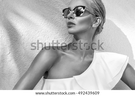 Portrait beautiful phenomenal stunning elegant sexy blonde model woman with perfect face wearing a sunglasses stands with elegant swinsuit on amazing view with palm tree shadow in Cannes, France