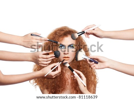 Portrait beautiful red long wavy, curly hair girl with make-up brushes near attractive face, many hands apply make up on woman face, - stock photo