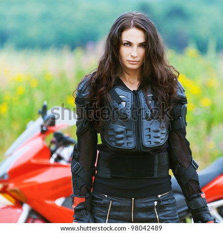 portrait beautiful sad dark-haired woman leather jacket standing alongside red motorcycle background summer green field - stock photo