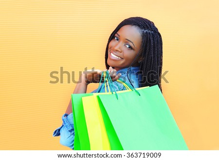 Portrait beautiful smiling african woman with shopping bags in city over orange background - stock photo