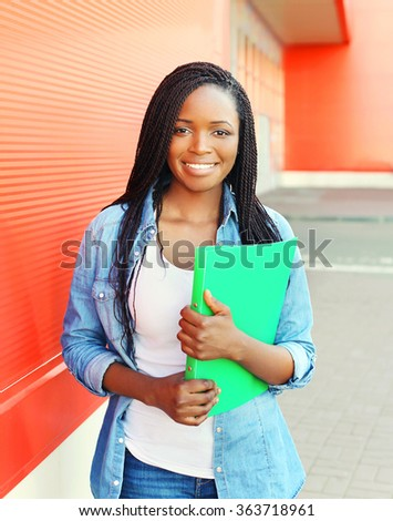 Portrait beautiful smiling young african woman with folder in city - stock photo