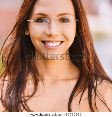 Portrait beautiful smiling young woman in glasses with crossed hands. - stock photo
