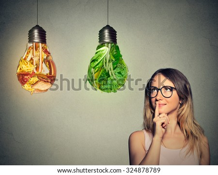 Portrait beautiful woman in glasses thinking looking up at junk food and green vegetables shaped as light bulb isolated on gray background. Diet choice right nutrition healthy lifestyle concept   - stock photo