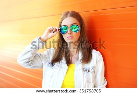 Portrait beautiful woman in sunglasses over colorful orange background