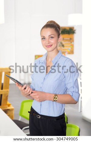Portrait beautiful woman on the background of modern business office. Modern businesswoman holding tablet computer on background office space.